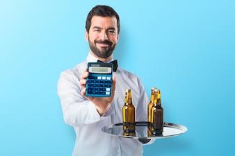 Garçom com garrafas de cerveja na bandeja segurando uma calculadora em fundo colorido