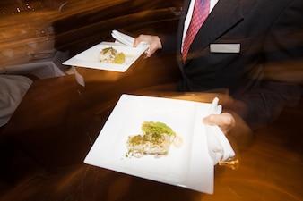 Garçonete movendo e segurando alimentos de bandeja para jantar no restaurante do hotel com técnica de câmera