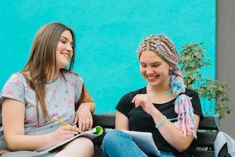 Garotas alegres estudando no banco