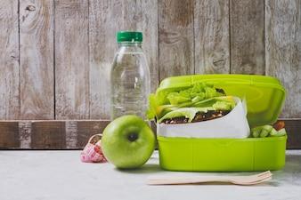 Garrafa de água e maçã ao lado de uma caixa de almoço