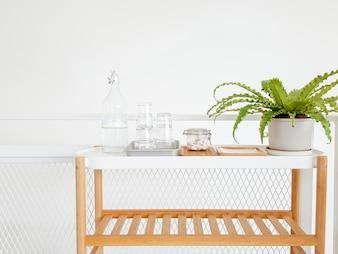 Garrafa de água na mesa de madeira no quarto branco do hotel. Ficus de flor verde. Artesanato doméstico. Ecologia