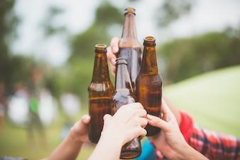 Garrafas de cerveja. Grupo de amigos que gostam de party.people estão bebendo cerveja e rindo. O cara toca violão. Todo mundo tem um ótimo humor. Horário de verão. Imagens de estilo de efeito vintage.