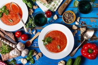 Gazpacho de sopa clássica saborosa saborosa e saborosa em pratos brancos em mesa azul rústica com pão, alho e especiarias. Conceito de comida para jantar. Vista do topo.