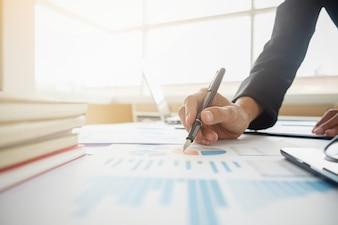 Gerente de mulher asiática colocando suas idéias e escrevendo plano de negócios no local de trabalho, fazendo anotações em documentos na mesa no escritório, cor vintage, foco seletivo. Conceito de negócios.