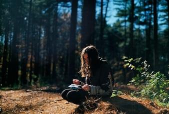 Menina sentada na floresta