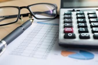 Gráficos financeiros na mesa com laptop, calculadora, caneta e conceito de negócios de óculos