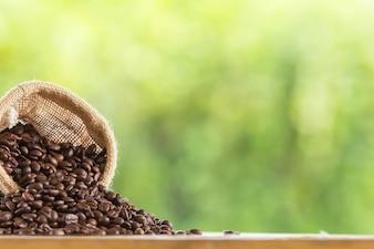 Grão de café em saco na mesa de madeira contra grunge verde borrão de fundo
