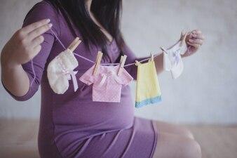 Grávida, segurando, bebê, roupa