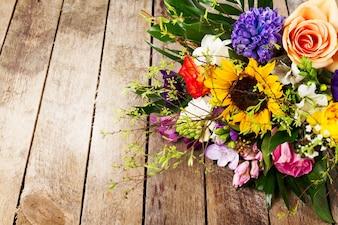 Grupo bonito de flores no fundo de madeira. Horizontal. Vista de cima.