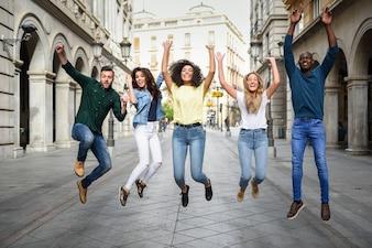 Grupo de amigos pulando juntos ao ar livre