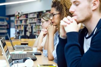 Grupo de amigos que estudam em uma biblioteca universitária.