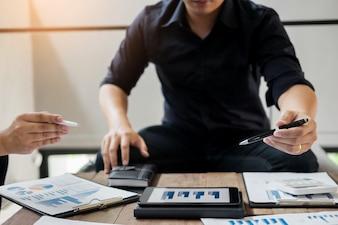 Grupo de empresários bem-sucedidos que discutem papelada e usando um laptop juntos, trabalho em equipe e conceito de brainstorming.