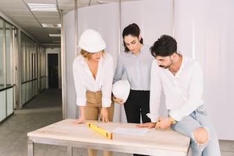 Grupo de engenheiros que se inclina sobre a mesa