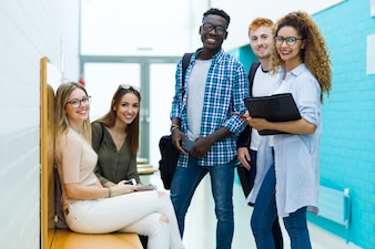 Grupo de estudantes jovens felizes olhando a câmera em uma universidade.