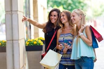 Grupo de meninas bonitas que olham a janela da loja.