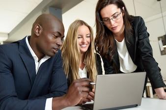 Grupo multiétnico de três empresários reunidos em um escritório moderno. Duas mulheres caucasianas e um homem negro vestindo um terno olhando para um computador laptop.