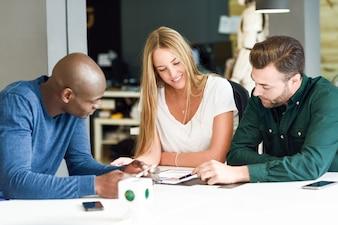 Grupo multiétnico de três jovens que estudam juntos