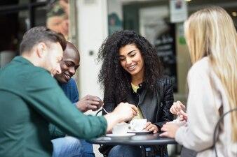 Grupo multirracial de quatro amigos tomando um café juntos