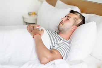 Guy dormindo com as mãos sobre o peito