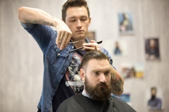 Hairstylist fazendo corte de cabelo para cliente masculino