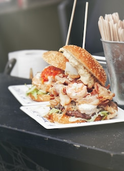 Hamburger com um monte de comida preso com uma vara