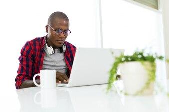 Handsome young man usando seu laptop em casa.
