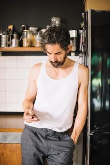 Homem adulto com telefone na cozinha