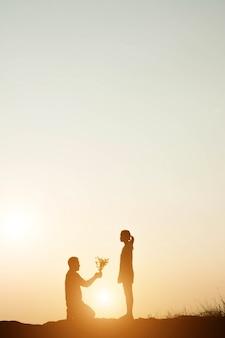 Homem ajoelhado ao pôr do sol dá o ramalhete a uma mulher