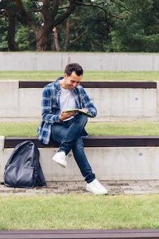 Homem alegre lendo no parque