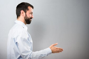 Homem bonito com barba fazendo um acordo no fundo texturizado