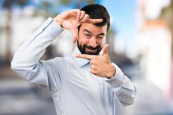 Homem bonito com barba focada com os dedos no fundo não focado