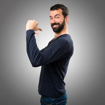 Homem bonito com barba orgulhoso de si mesmo em fundo cinza