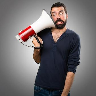 Homem bonito com barba segurando um megafone em fundo cinza
