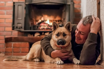 Homem bonito com cachorro sentado no tapete em casa. Homem maduro que relaxa em casa com cão de estimação na frente da lareira