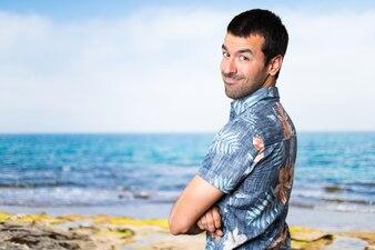 Homem bonito com camisa de flor com os braços cruzados na praia