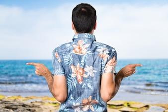 Homem bonito com camisa de flores apontando para os laterais tendo dúvidas na praia
