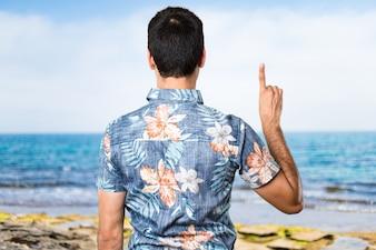 Homem bonito com camisa de flores contando um na praia