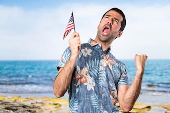 Homem bonito com camisa de flores segurando uma bandeira americana na praia