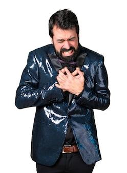 Homem bonito com casaco de lantejoula com dor no coração