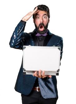 Homem bonito com casaco de lantejoulas segurando uma maleta