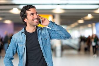 Homem bonito falando ao celular sobre fundo branco