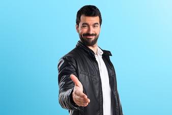 Homem com jaqueta de couro fazendo um acordo sobre fundo colorido
