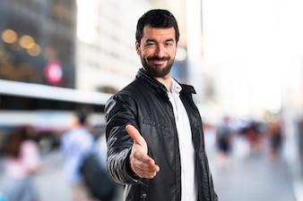 Homem com jaqueta de couro fazendo um acordo