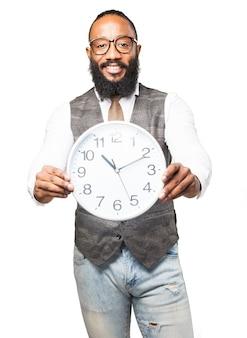 Homem com o laço, sorrindo e segurando um relógio