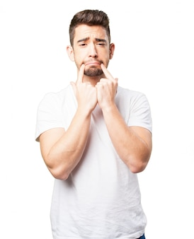 Homem com o rosto triste e dois dedos sobre os lábios