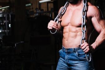 Homem com peito nu com corrente pesada