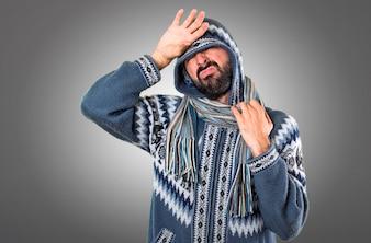 Homem com roupas de inverno com febre em fundo cinza