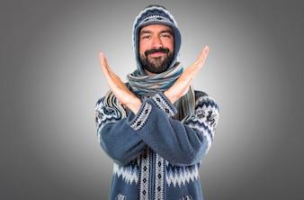 Homem com roupas de inverno fazendo nenhum gesto em fundo cinza