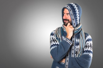 Homem com roupas de inverno olhando lateral em fundo cinza