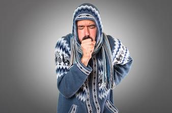Homem com roupas de inverno tossindo muito sobre fundo cinza